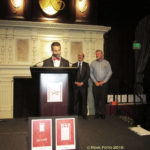 Okan Sengun at the podium with Ron Flynn and Bill Hirsh in the background